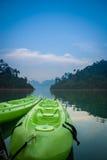 Duas canoas verdes no lago no tempo do twillight Imagem de Stock Royalty Free