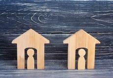 Duas casas de madeira com povos em um fundo preto O conceito do distrito, seus vizinhos Relações de boa vizinhança afford imagem de stock