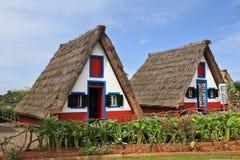 Duas casas rurais com o telhado thatched triangular Imagens de Stock