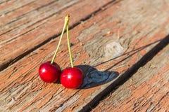 Duas cerejas em uma tabela de madeira Fotos de Stock