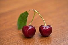 Duas cerejas maduras vermelhas com hastes e uma folha em uma tabela de madeira imagem de stock