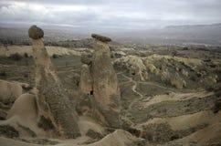 Duas chaminés feericamente em uma vez de nivelamento nebulosa em Cappadocia, Urgup, Turquia foto de stock royalty free