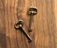 Duas chaves de bronze em uma tabela de madeira Imagens de Stock Royalty Free