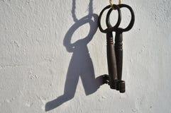 Duas chaves de esqueleto antigas que penduram de uma parede branca Imagens de Stock Royalty Free