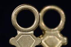 Duas chaves de relógio de bronze antigas do bolso que estão na escuridão Foto de Stock