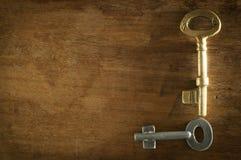 Duas chaves velhas colocadas em uma baixa luz chave do assoalho de madeira Fotografia de Stock Royalty Free