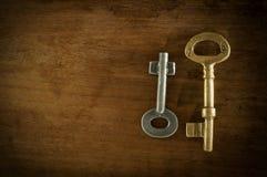 Duas chaves velhas colocadas em uma baixa luz chave do assoalho de madeira Imagens de Stock Royalty Free