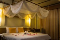Duas cisnes brancas de toalha e p?talas cor-de-rosa vermelhas na cama, decora??o da lua de mel foto de stock royalty free