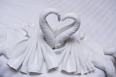 Duas cisnes feitas das toalhas que formam o olhar como a forma do coração na cama Fotos de Stock