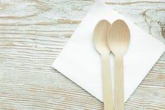 Duas colheres de madeira que encontram-se em um guardanapo em um café na tabela de madeira Fotos de Stock Royalty Free