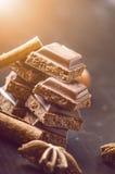 Duas construções do chocolate em um fundo escuro energia e açúcar Barra quebrada Pilha dos blocos do chocolate foto de stock