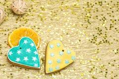 Duas cookies dadas forma coração do pão-de-espécie no fundo do ouro Foto de Stock Royalty Free