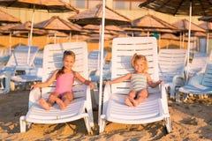 Duas crianças adoráveis que tomam sol em uma praia Imagem de Stock Royalty Free