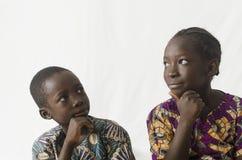 Duas crianças africanas que pensam com mãos em seus queixos, isolado Imagem de Stock