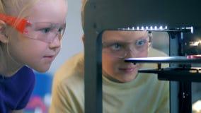 Duas crianças agitados estão olhando uma experiência científica com interesse vídeos de arquivo