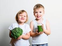 Duas crianças bonitas do divertimento com batidos e brócolis verdes Helthy Imagens de Stock