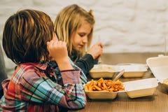 Duas crianças bonitos comem a massa dos espaguetes no restaurante do fast food fotografia de stock royalty free