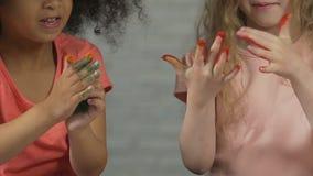 Duas crianças bonitos que cobrem as mãos pequenas na pintura colorida, cofre forte do produto para crianças filme