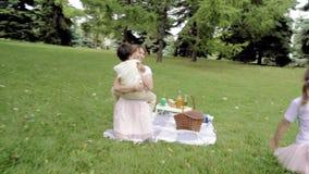 Duas crianças bonitos que correm nos braços da mamã no gramado filme