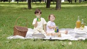 Duas crianças bonitos que sentam e que bebem bebidas fora
