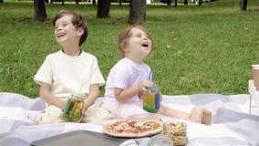 Duas crianças bonitos que têm o divertimento e que bebem bebidas fora