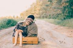 Duas crianças com a grande mala de viagem amarela na estrada no estilo retro Fotos de Stock Royalty Free