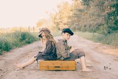 Duas crianças com a grande mala de viagem amarela na estrada no estilo retro Imagem de Stock