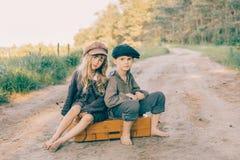 Duas crianças com a grande mala de viagem amarela na estrada no estilo retro Imagens de Stock Royalty Free