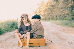 Duas crianças com a grande mala de viagem amarela na estrada no estilo retro Imagens de Stock