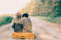 Duas crianças com a grande mala de viagem amarela na estrada no estilo retro Foto de Stock