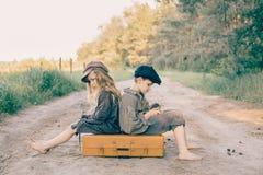 Duas crianças com a grande mala de viagem amarela na estrada no estilo retro Foto de Stock Royalty Free