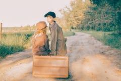 Duas crianças com a grande mala de viagem amarela na estrada no estilo retro Fotografia de Stock
