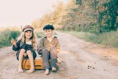 Duas crianças com a grande mala de viagem amarela na estrada no estilo retro Imagem de Stock Royalty Free