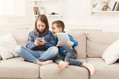 Duas crianças com os dispositivos no sofá em casa fotos de stock royalty free
