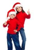 Duas crianças com polegares levantam o sinal e a Santa Fotografia de Stock
