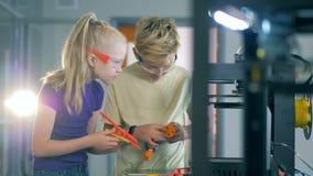 Duas crianças curiosas estão compondo elementos para um mecanismo experimental video estoque