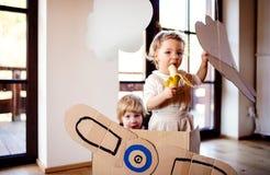 Duas crianças da criança com o plano da caixa que joga dentro em casa, conceito de voo fotos de stock