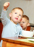 Duas crianças das crianças dos meninos dos irmãos que comem a refeição da manhã do café da manhã dos flocos de milho em casa. Fotos de Stock