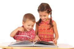 Duas crianças de sorriso que lêem o livro na mesa Foto de Stock Royalty Free