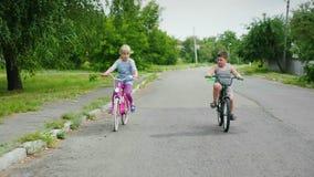 Duas crianças despreocupadas - uma menina e um menino montam bicicletas na rua tiro do steadicam vídeos de arquivo