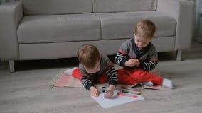 Duas crianças dos irmãos gêmeos tiram junto os marcadores que sentam-se no assoalho video estoque