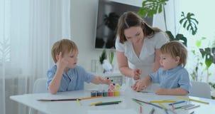 Duas crianças dos meninos e da mãe são contratadas no desenvolvimento criativo que faz trabalhos de casa pelo manejo no papel E filme