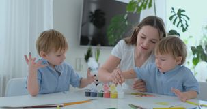 Duas crianças dos meninos e da mãe são contratadas no desenvolvimento criativo que faz trabalhos de casa pelo manejo no papel E video estoque