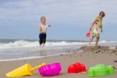 Duas crianças e brinquedos plásticos coloridos na praia Fotos de Stock Royalty Free