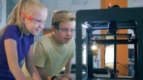 Duas crianças em um trabalho de laboratório com equipamento inovativo moderno, fim da escola acima video estoque