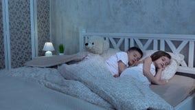 Duas crianças encontram-se na cama e no sono video estoque