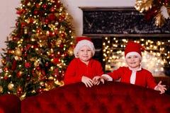 Duas crianças engraçadas bonitos vestidas em trajes de Santa espreitam para fora atrás de um sofá vermelho de veludo imagem de stock royalty free