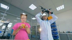 Duas crianças estão jogando com um quadcopter, zangão em um laboratório vídeos de arquivo