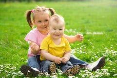 Duas crianças estão sentando-se no prado verde imagem de stock