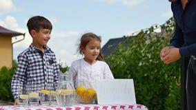 Duas crianças estão vendendo a limonada em um suporte de limonada caseiro em um dia ensolarado com um sinal do preço para um empr vídeos de arquivo